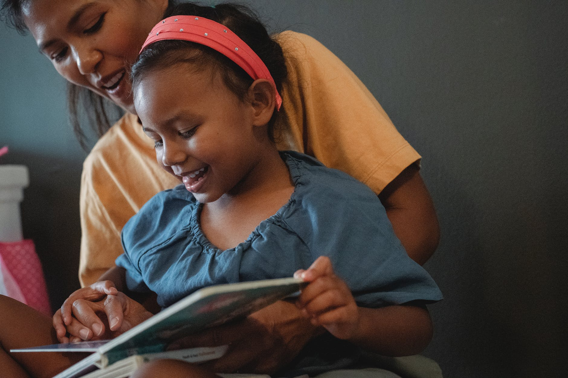 positive crop asian mother with daughter reading book