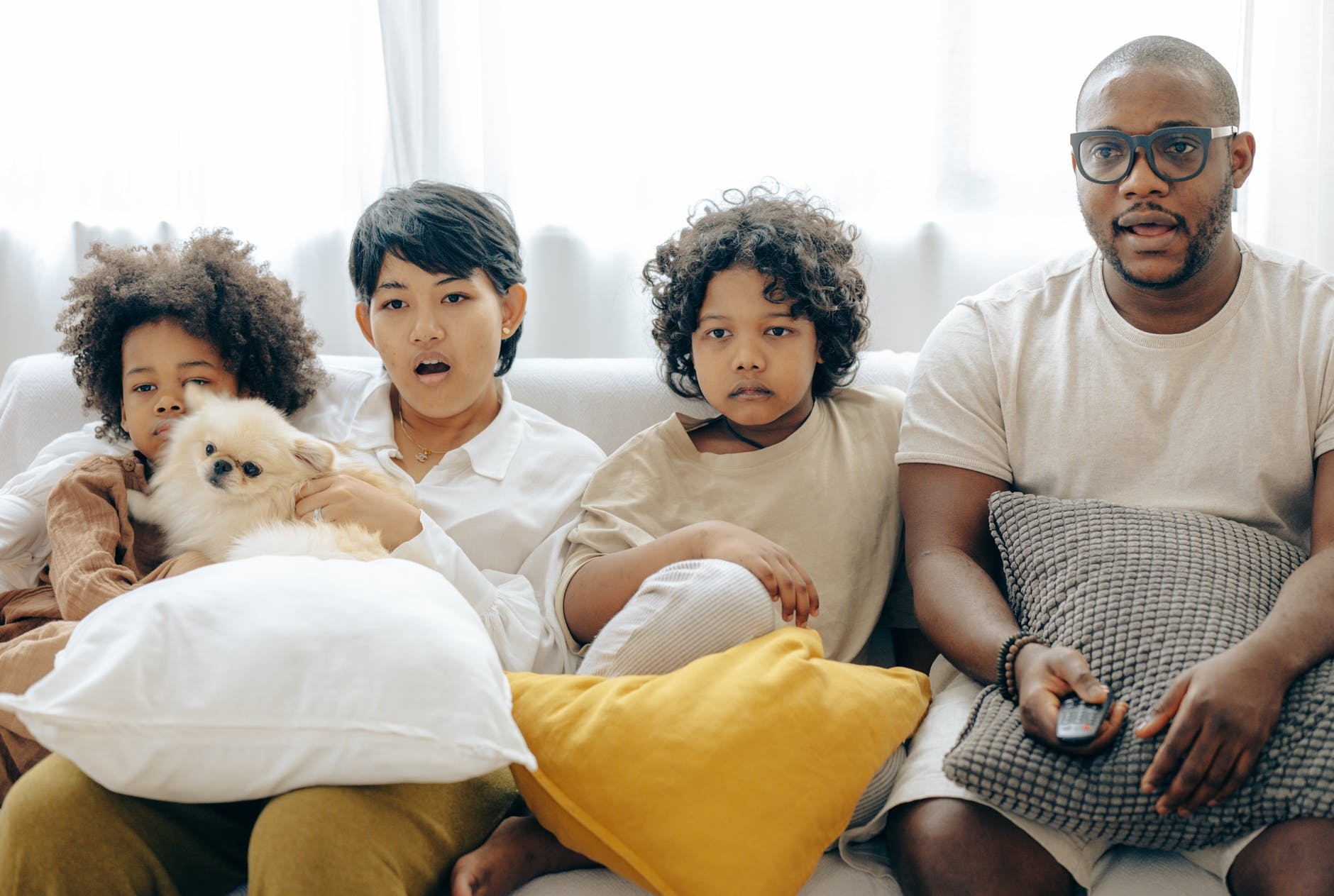 interested multiracial family watching tv on sofa together with dog